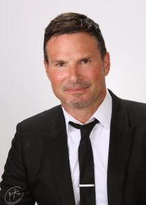 Headshot of Justin Kohll wearing a black suit and tie