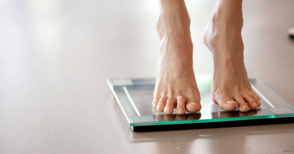 Woman stepping on scale checking weight loss